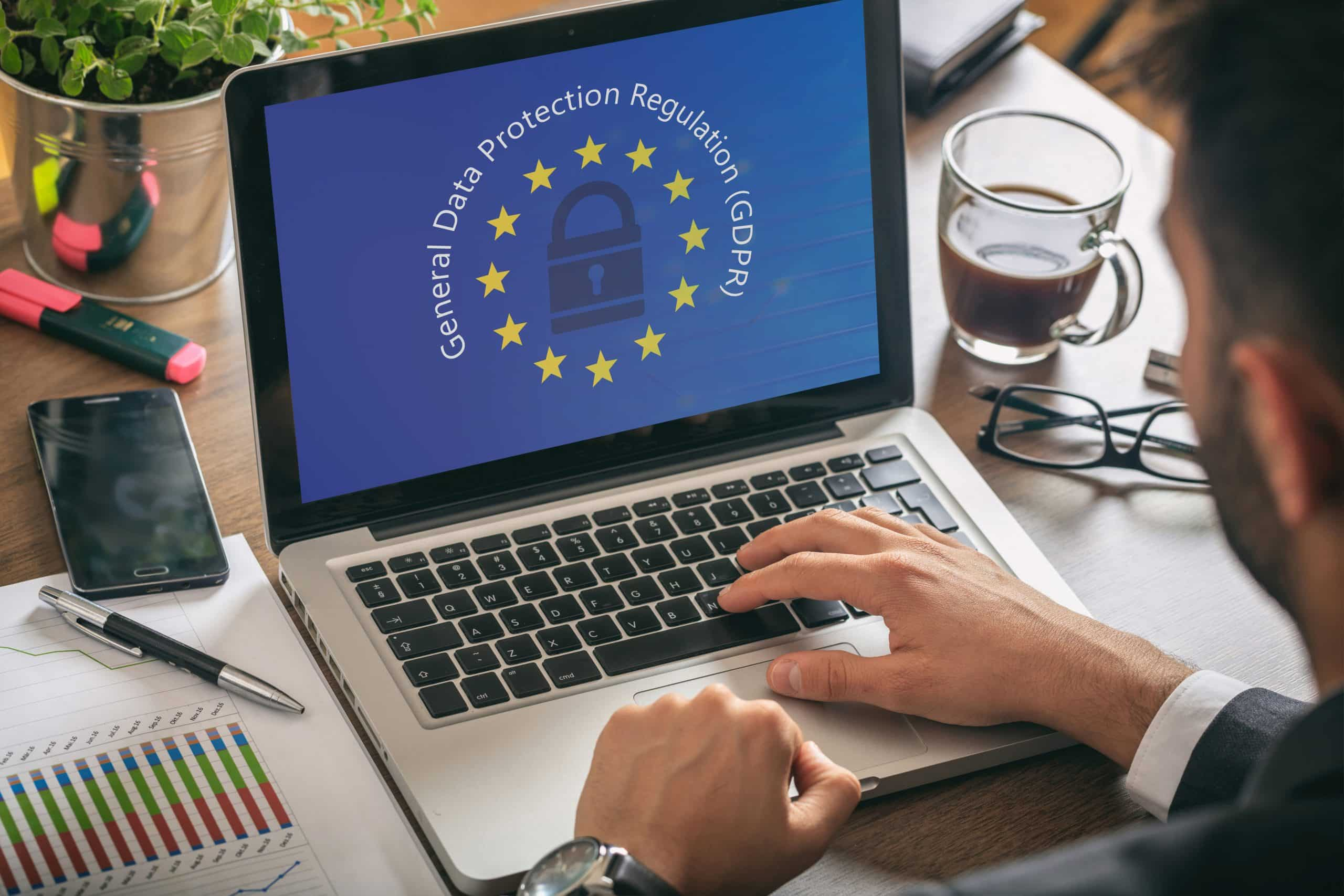 EU GDPR. Man working with a computer, General Data Protection Regulation and European Union flag on the screen