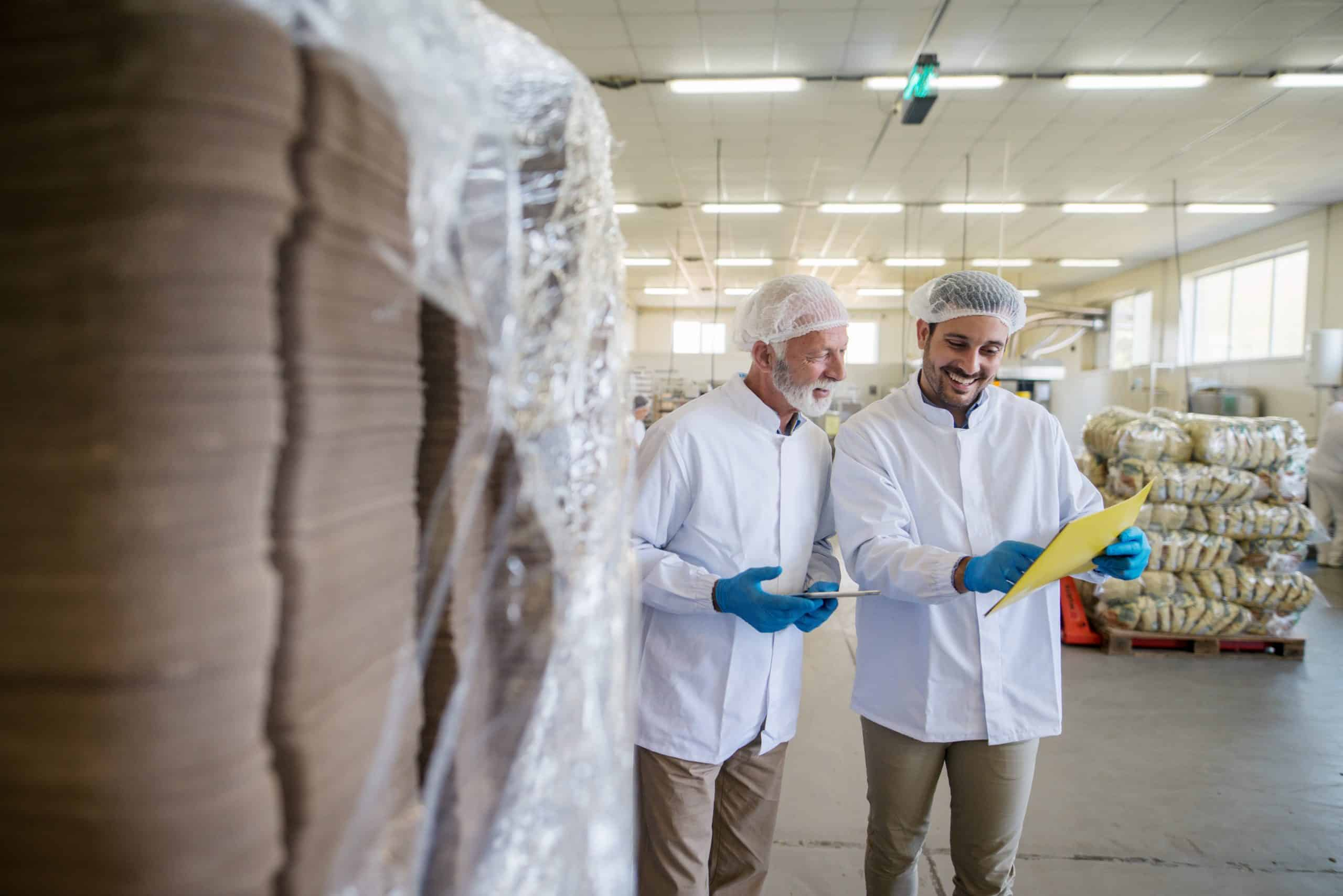 Two male managers in sterile clothes standing in warehouse and checking documents of package prepared for transport.
