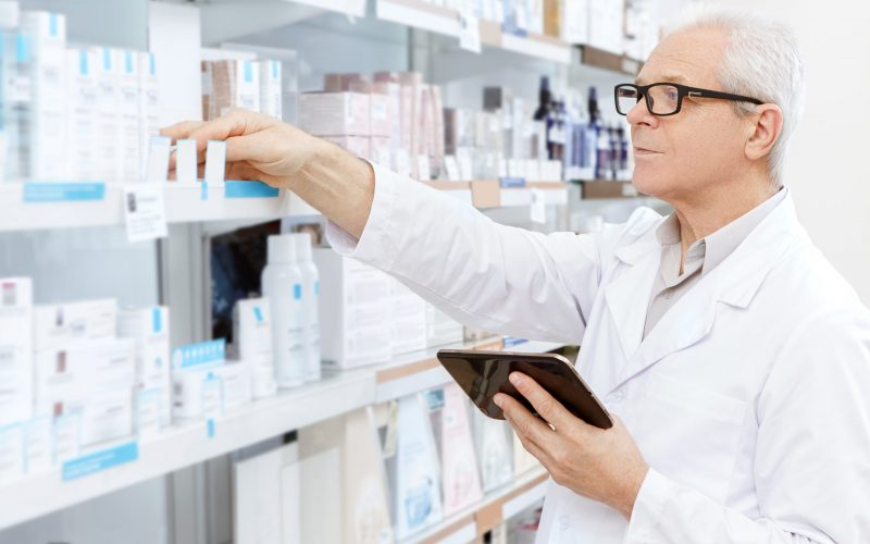 Running his business online. Elderly pharmacist checking stock in an aisle at his pharmacy ordering medications online using digital tablet running his small business pharmacy online shopping concept
