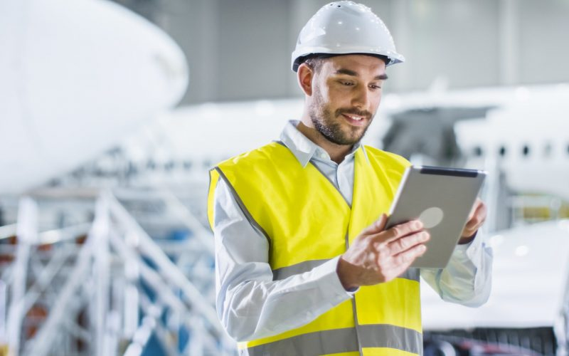 Portrait of Aircraft Maintenance Mechanic in Safety Vest using Tablet Computer