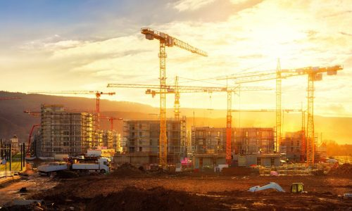 Large construction site including several cranes working on a building complex, illumined by warm gold sunlight