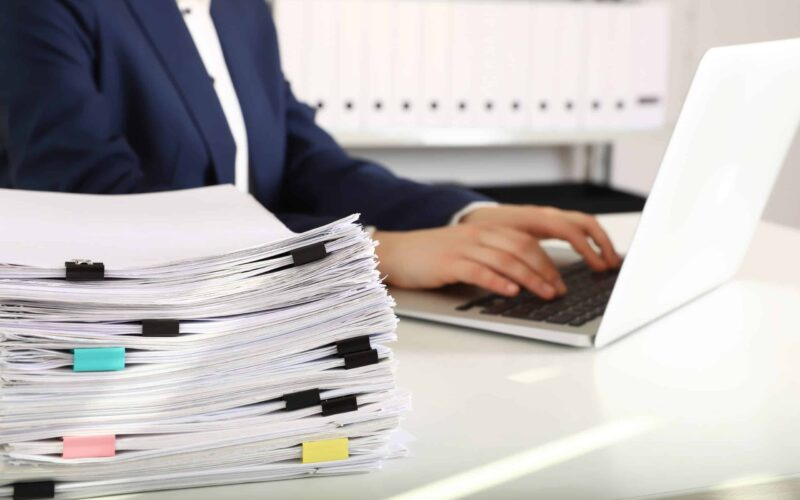 Stack of documents and woman working with laptop at table in office, closeup